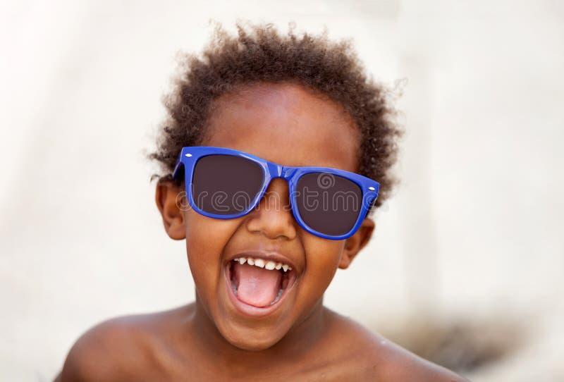 Criança afro-americana engraçada com óculos de sol azuis foto de stock