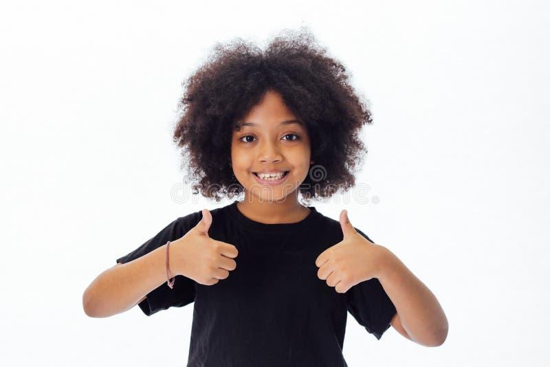 Criança afro-americano adorável e alegre com o penteado afro que dá os polegares acima foto de stock