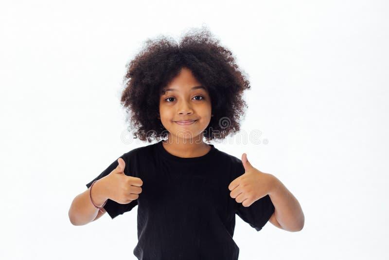 Criança afro-americano adorável e alegre com o penteado afro que dá os polegares acima imagens de stock