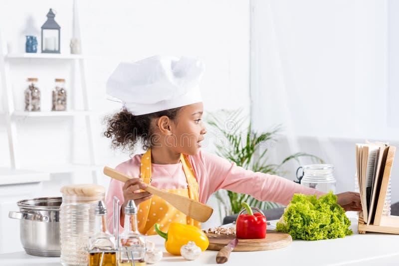 criança afro-americano adorável no cozimento do chapéu do avental e do cozinheiro chefe fotos de stock