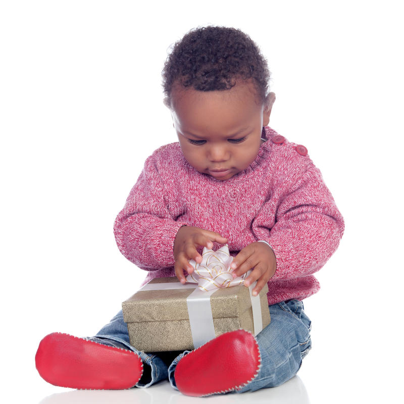 Criança afro-americano adorável que joga com uma caixa de presente fotografia de stock