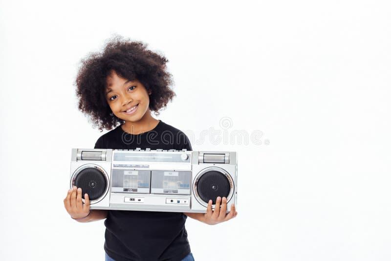 Criança afro-americano bonito e sorrindo que guarda um jukebox musical imagem de stock