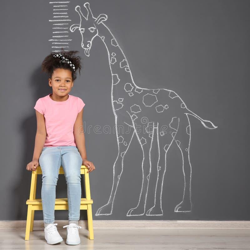 Criança afro-americano perto da parede cinzenta com o desenho do girafa do giz foto de stock