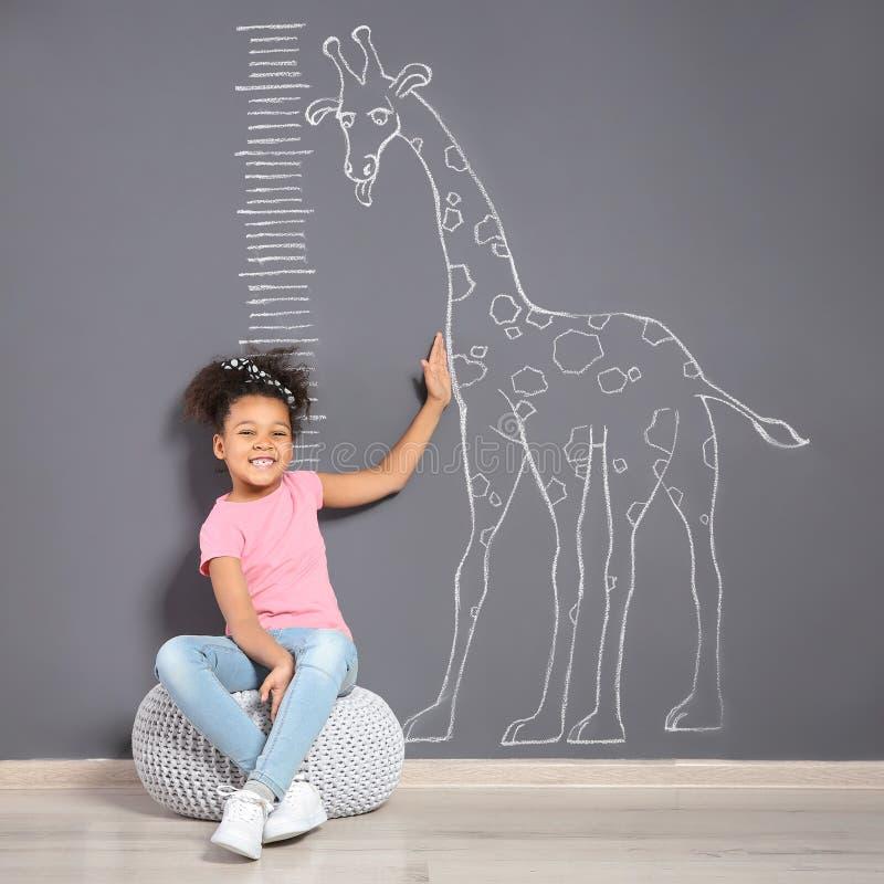 Criança afro-americano perto da parede cinzenta com o desenho do girafa do giz foto de stock royalty free