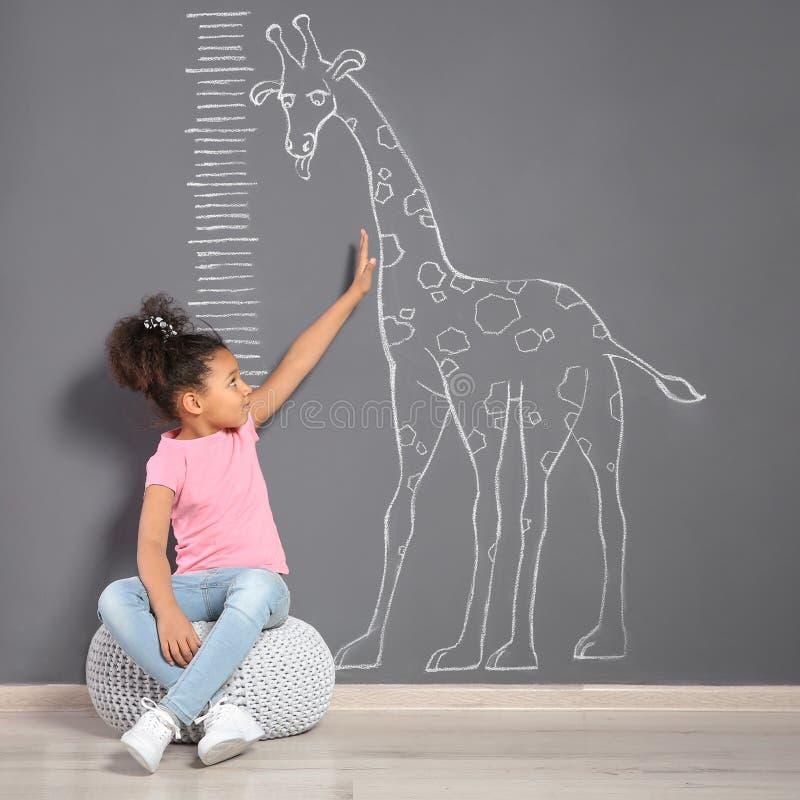 Criança afro-americano perto da parede cinzenta com o desenho do girafa do giz imagem de stock
