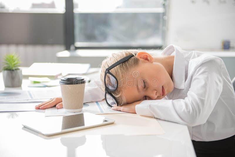 A criança agradável está dormindo no escritório fotografia de stock