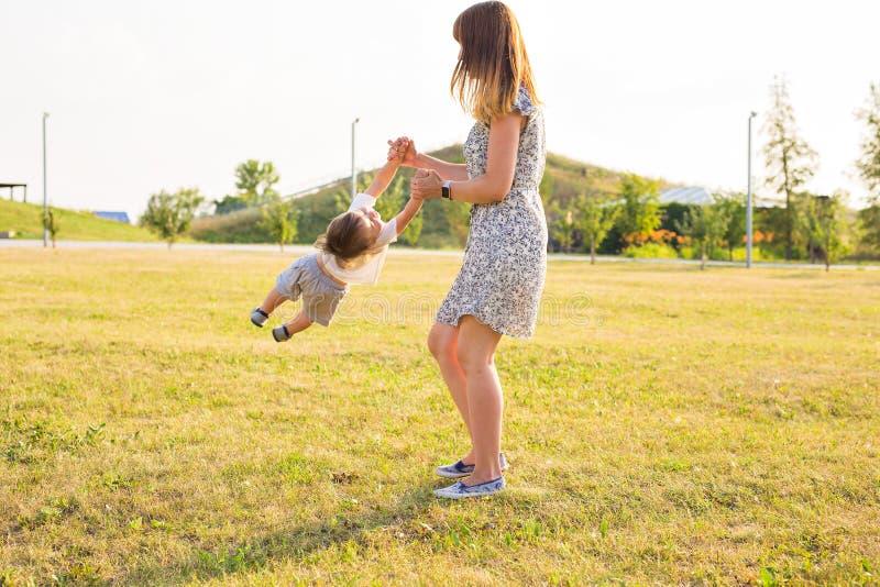 Criança alegre bonito com jogo da mãe fora no parque fotos de stock royalty free
