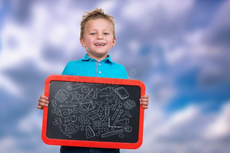 Criança alegre com placa vazia com símbolos a bordo imagem de stock