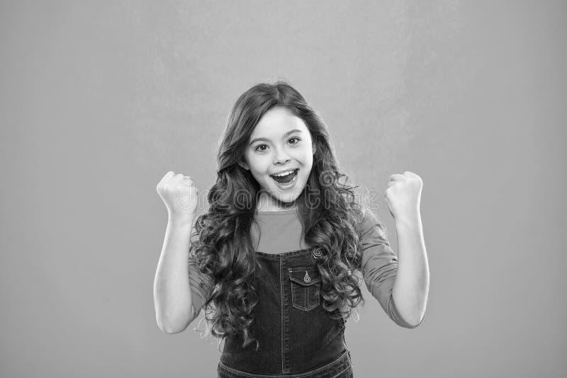 A criança alegre comemora a vitória Sorriso feliz longo do cabelo encaracolado da criança bonito da menina Psicologia e desenvolv imagens de stock royalty free