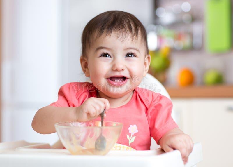 Criança alegre do bebê que come o alimento próprio com uma colher imagens de stock