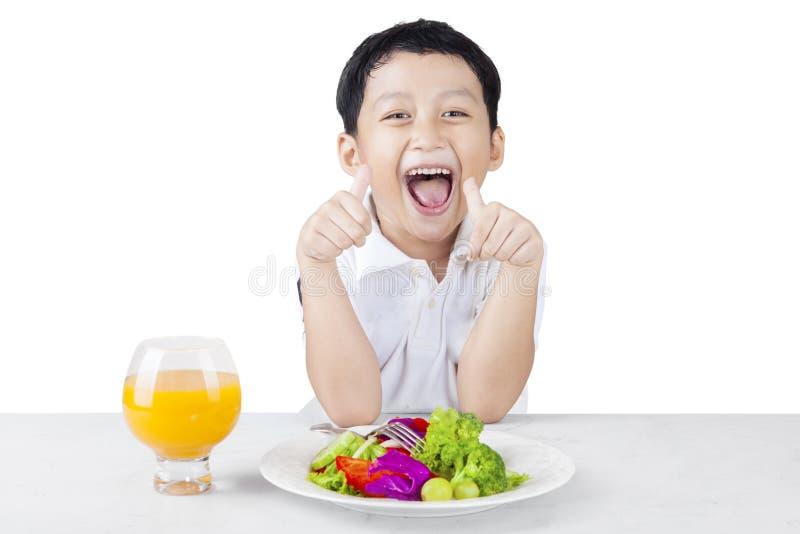 Criança alegre que come a salada e o suco foto de stock