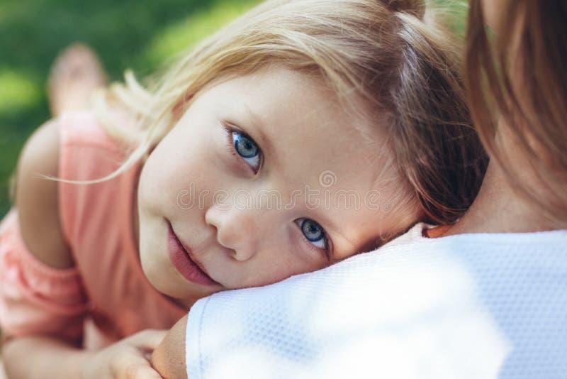Criança alegre que descansa com mamã imagem de stock