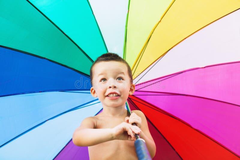 Criança alegre que gira o guarda-chuva colorido grande fotografia de stock