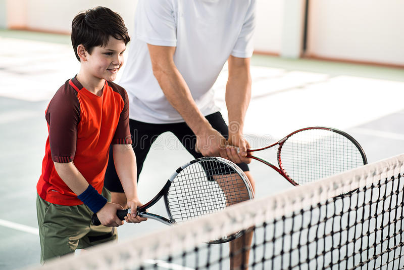 Criança alegre que joga o tênis com pai imagem de stock royalty free