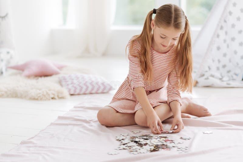 Criança amaneirado boa que joga o jogo do enigma imagem de stock