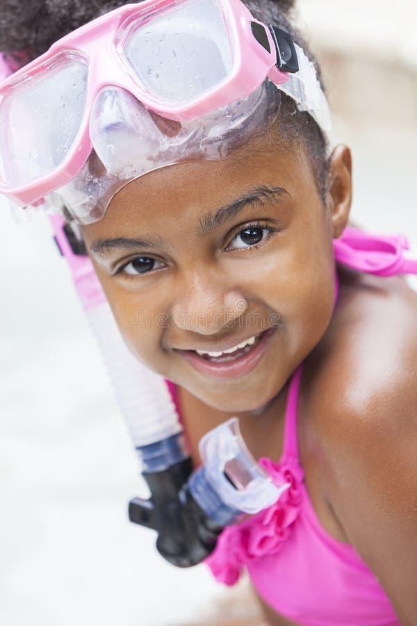 Criança americana africana da menina na piscina com óculos de proteção imagens de stock royalty free