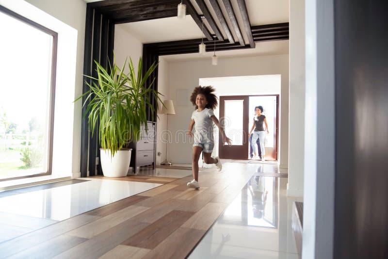 Criança americana entusiasmado que corre no corredor que entra na casa moderna grande imagem de stock