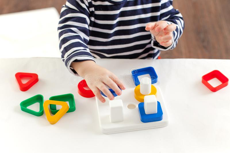 A criança 1,5 anos de assento velho na tabela e jogo com um brinquedo tornando-se, técnica de Montessori, as mãos do ` s da crian imagem de stock