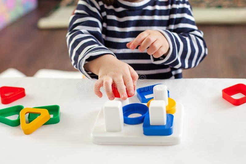 A criança 1,5 anos de assento velho na tabela e jogo com um brinquedo tornando-se, técnica de Montessori, as mãos do ` s da crian imagens de stock royalty free