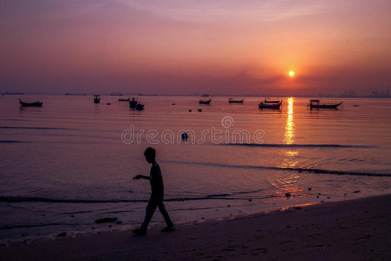 A criança aprecia o sunrse Os barcos mostram em silhueta com reflexão alaranjada do céu e da água dos barcos foto de stock royalty free