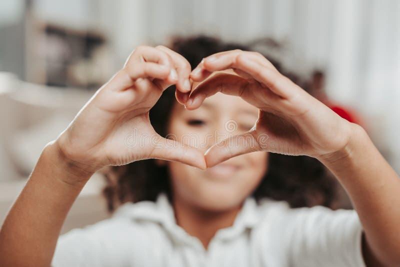 Criança apreciada que olha através dos dedos dados forma coração imagem de stock