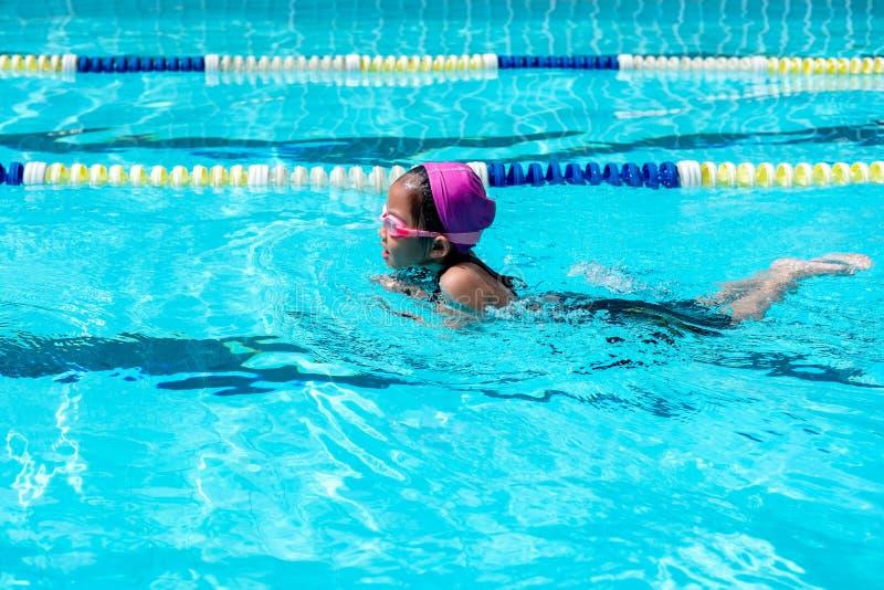 A criança aprende como nadar na classe da natação imagem de stock royalty free