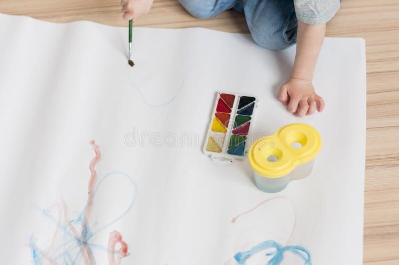 A criança aprende guardar a escova e tirá-la com aquarelas fotografia de stock
