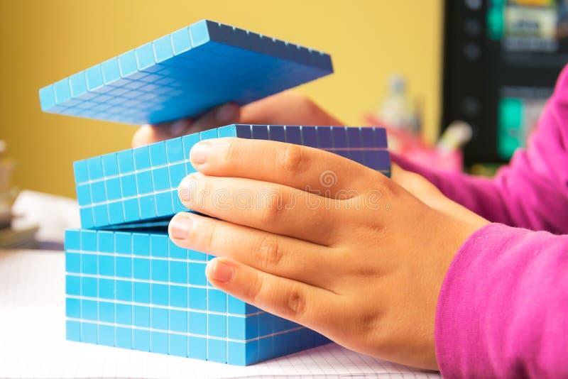A criança aprende a matemática, o volume e a capacidade Para aprender o modelo usa um cubo tridimensional foto de stock