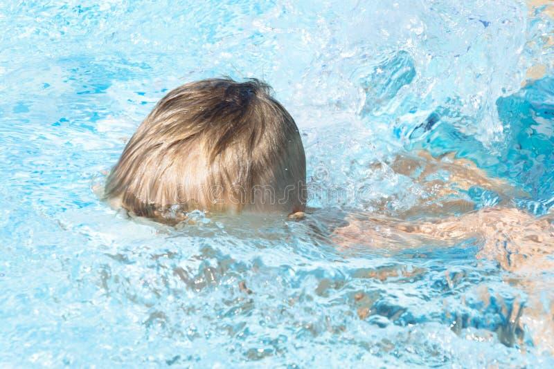 A criança aprende nadar, mergulho na associação azul com divertimento - saltar profundamente para baixo debaixo d'água com espirr fotografia de stock royalty free