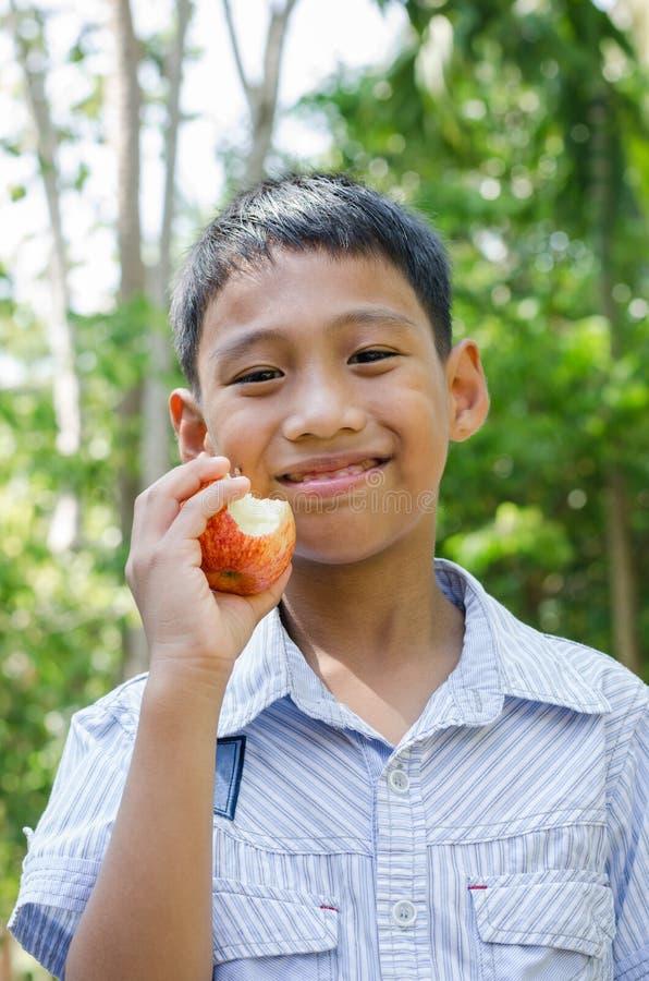 A criança asiática aprecia comer Apple fotografia de stock royalty free