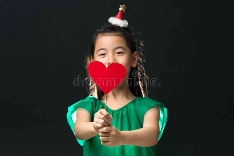 A criança asiática bonito da menina vestiu-se em um vestido verde que guarda um ornamento do Natal e uma vara do coração em um fu imagens de stock