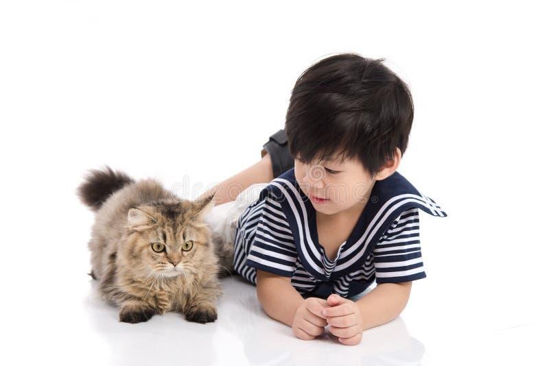 Criança asiática bonito que encontra-se com gato de gato malhado foto de stock royalty free