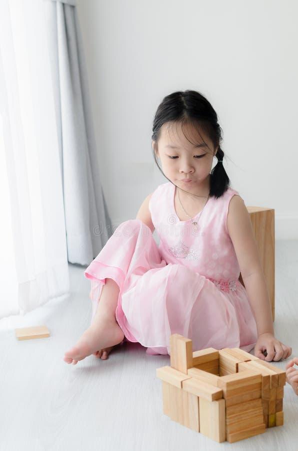 Criança asiática bonito que joga o bloco de madeira fotos de stock royalty free