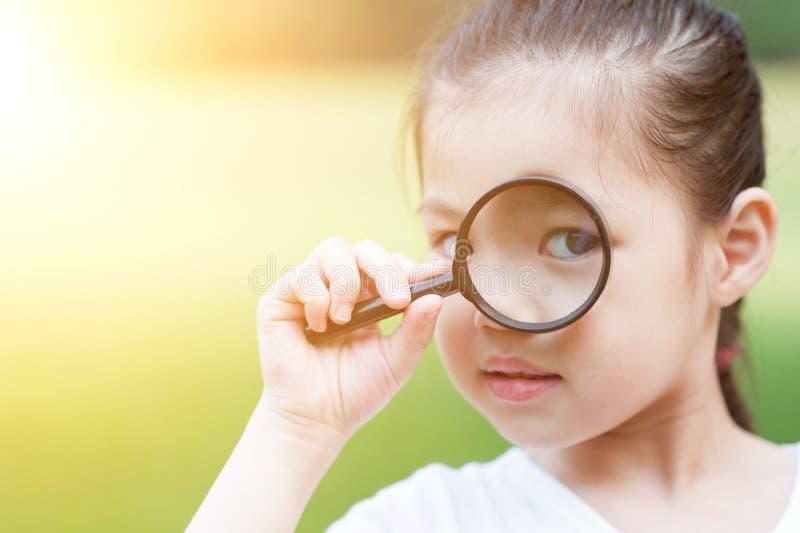 Criança asiática com vidro da lente de aumento em fora fotografia de stock