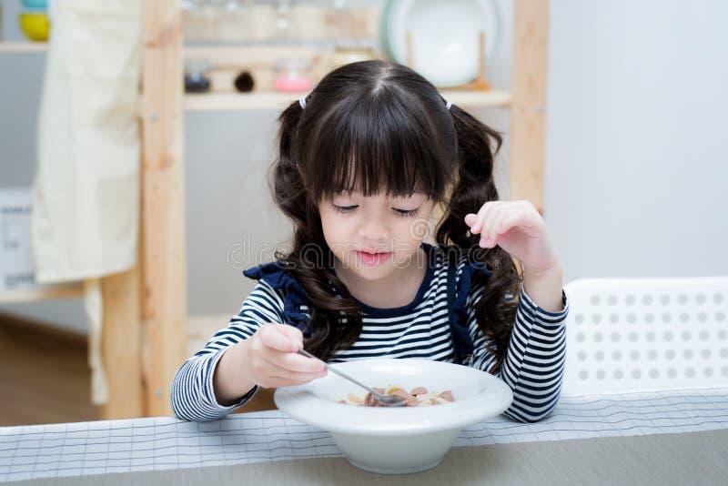 A criança asiática come o cereal e o leite imagem de stock royalty free