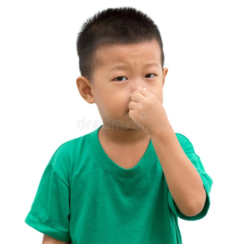 A criança asiática comprime seu nariz foto de stock