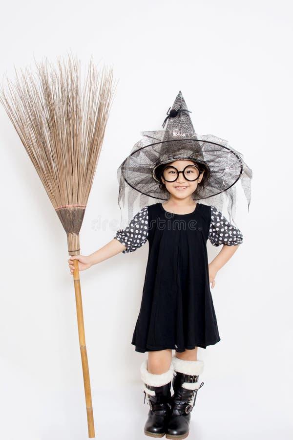 Criança asiática da bruxa que guardara a vassoura mágica fotos de stock royalty free