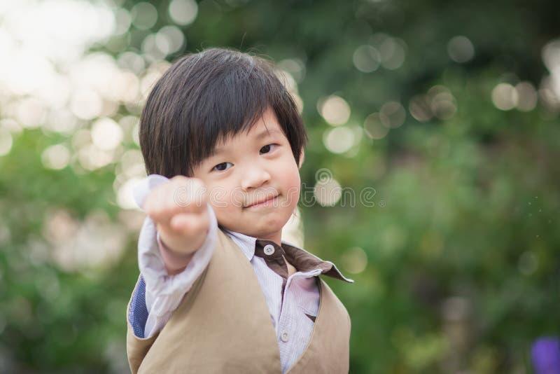 A criança asiática da confiança mostra sua mão foto de stock