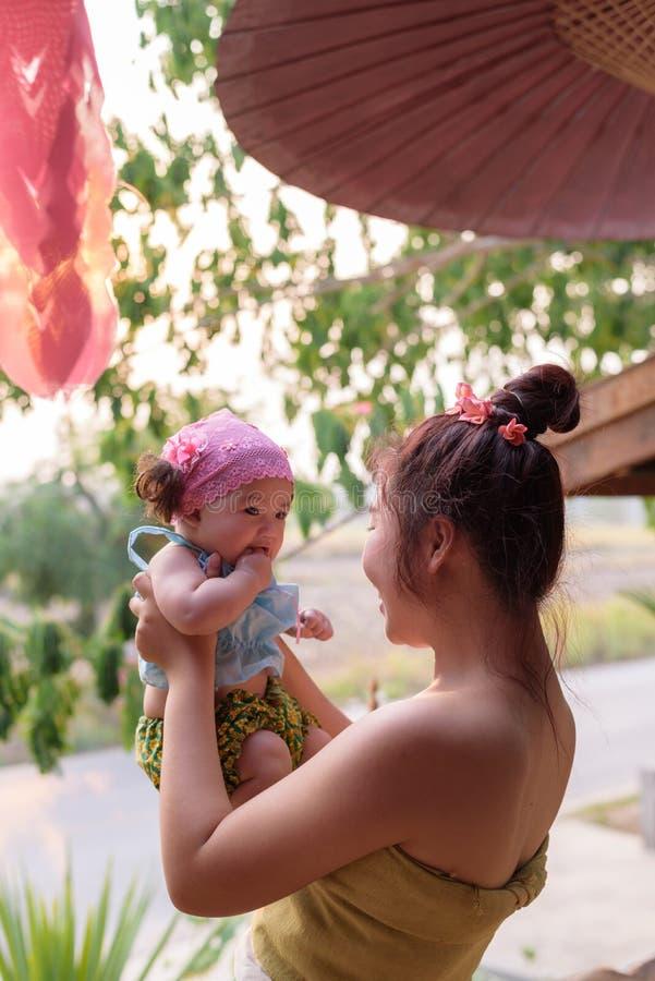 Criança asiática da posse da mamã à disposição imagem de stock