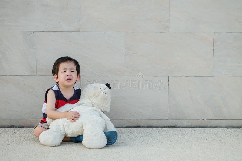 A criança asiática do close up está gritando com urso que a boneca se senta em fundo textured da parede de tijolo imagem de stock royalty free