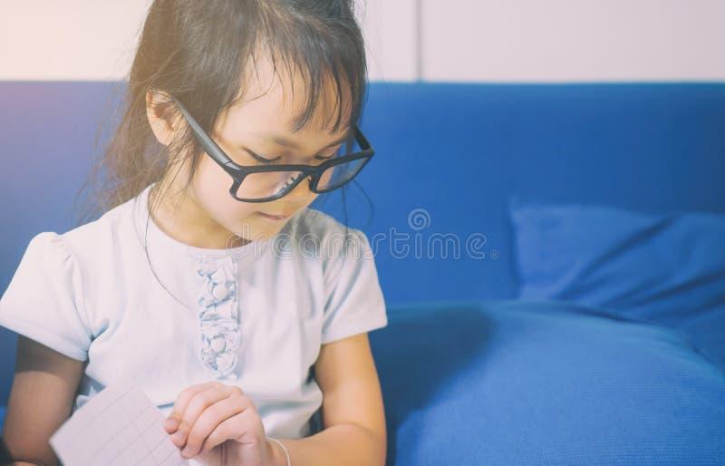 A criança asiática dos vidros Nerdy está lendo um livro fotografia de stock royalty free