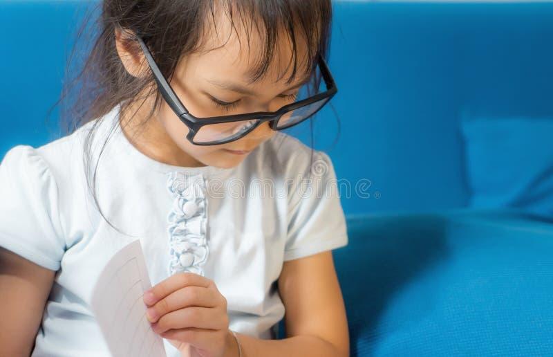 A criança asiática dos vidros Nerdy está lendo um livro foto de stock royalty free
