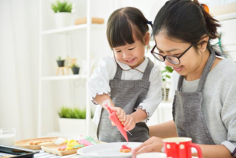 Criança asiática e mãe nova que decoram cookies imagens de stock