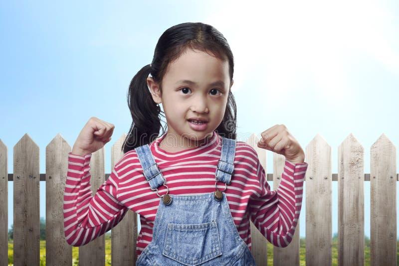 Criança asiática engraçada que mostra o músculo em sua mão foto de stock