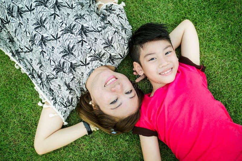 Criança asiática feliz com jogo da mãe fora no parque fotografia de stock