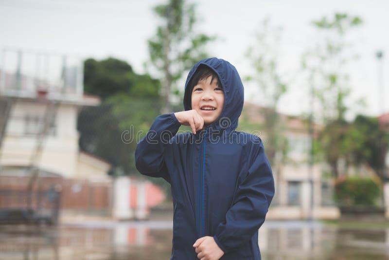 Criança asiática na capa de chuva azul foto de stock