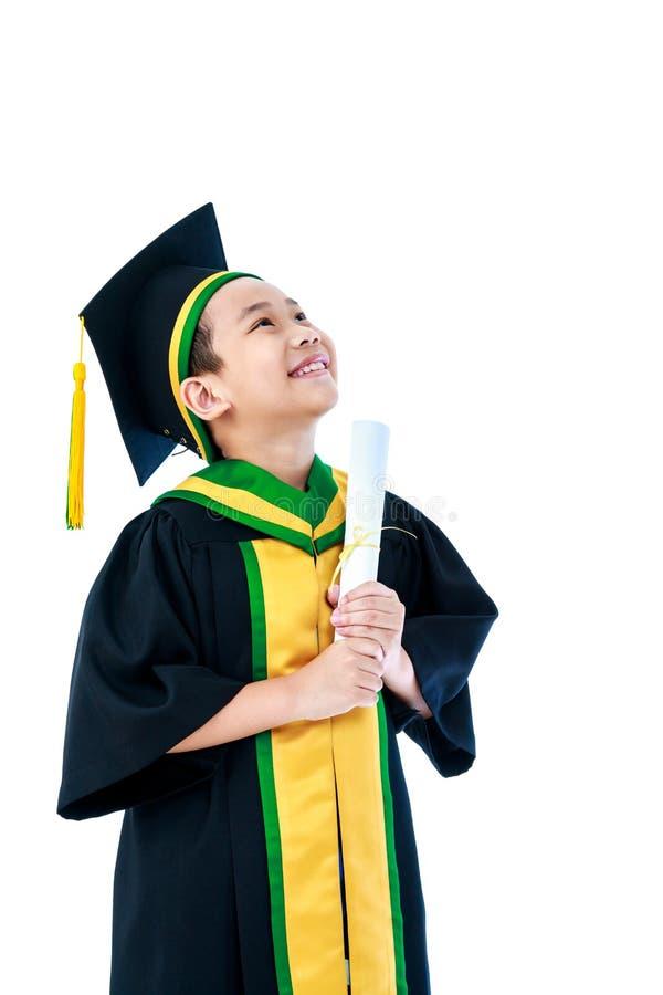Criança asiática no sorriso do vestido da graduação e no certificado do diploma fotografia de stock