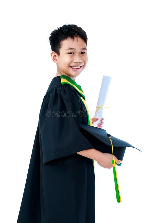 Criança asiática no vestido da graduação com certificado e tampão do diploma fotografia de stock royalty free