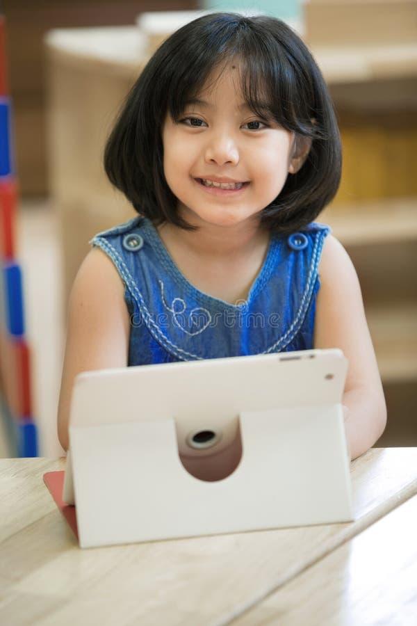 Criança asiática pequena que joga com uma tabuleta do computador imagens de stock
