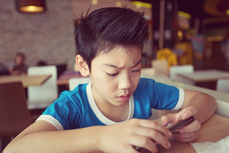 Criança asiática pequena que joga com uma tabuleta do computador fotos de stock royalty free